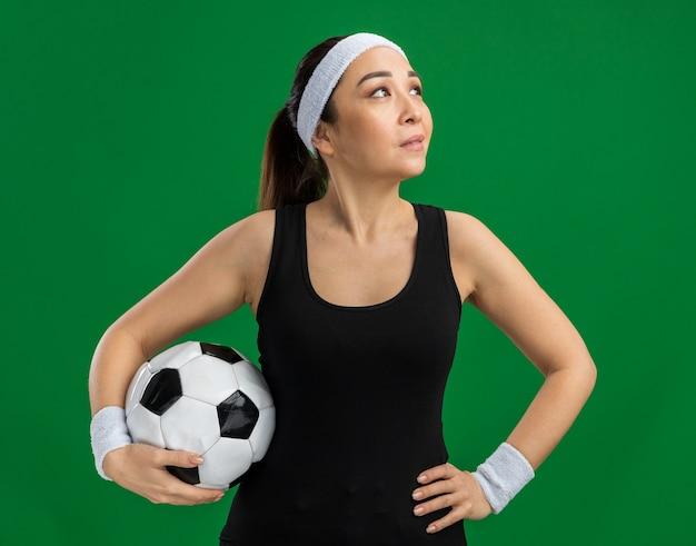 Junge fitness-frau mit stirnband, die fußball hält und mit einem lächeln auf dem gesicht zur seite schaut, das über grüner wand steht?