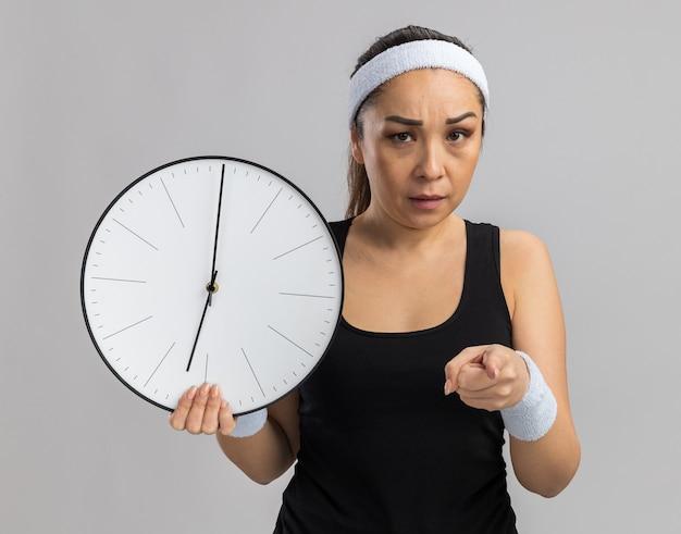 Junge fitness-frau mit stirnband und armbinden, die eine wanduhr hält, die mit dem zeigefinger zeigt, der wütend über die weiße wand steht?