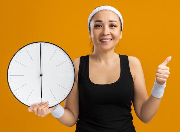 Junge fitness-frau mit stirnband und armbinden, die eine wanduhr hält und fröhlich lächelt und daumen nach oben zeigt