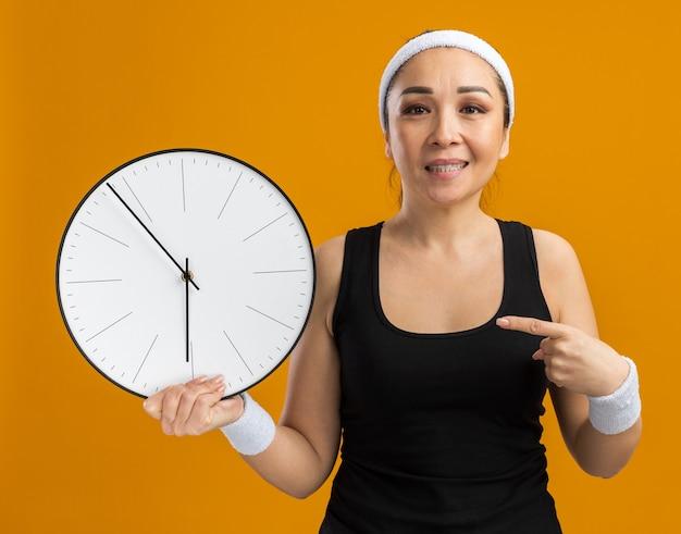 Junge fitness-frau mit stirnband und armbinden, die eine wanduhr hält und mit dem zeigefinger darauf zeigt, lächelt selbstbewusst über orangefarbener wand