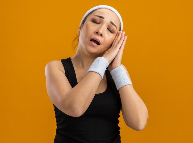 Junge fitness-frau mit stirnband und armbinden, die hände zusammenhalten und mit geschlossenen augen schlafende geste machen