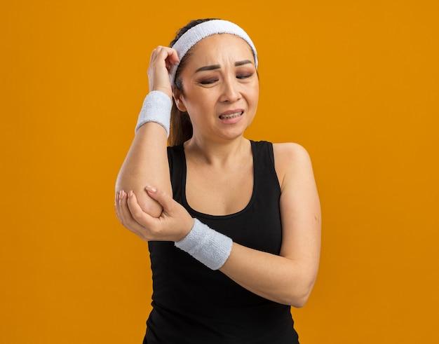 Junge fitness-frau mit stirnband und armbinden, die ihren ellbogen berühren und sich unwohl fühlen, schmerzen über der orangefarbenen wand stehend fühlen