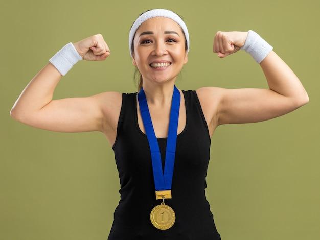 Junge fitness-frau mit stirnband und armbinden mit goldmedaille um den hals, die selbstbewusst lächelt und fäuste hebt, die stärke und macht über grüner wand zeigen