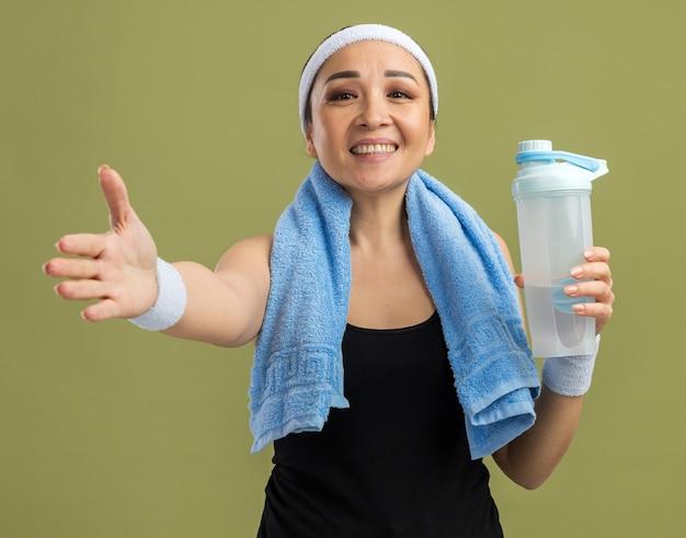 Junge fitness-frau mit stirnband und armbinden mit handtuch um den hals hält wasserflasche lächelnd freundlich und bietet handgruß über grüner wand stehend