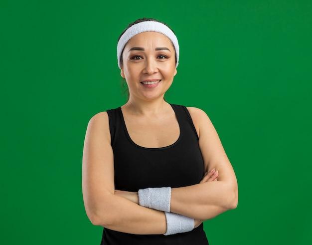 Junge fitness-frau mit stirnband und armbinden mit lächeln im gesicht mit verschränkten armen über grüner wand stehend