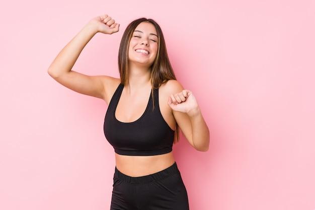 Junge fitness kaukasische frau isoliert, die einen besonderen tag feiert, springt und arme mit energie erhebt