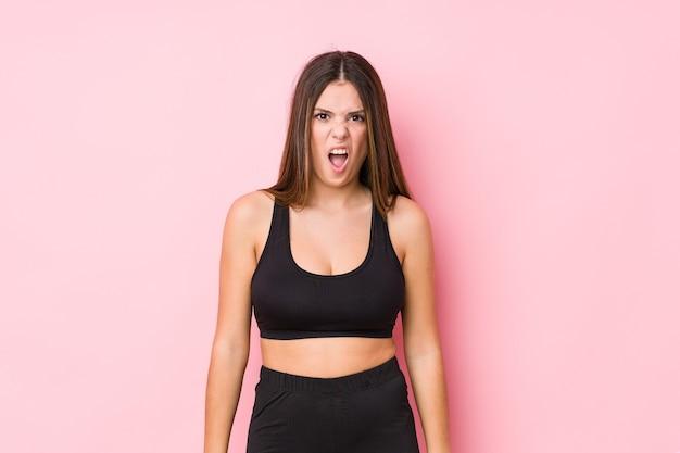 Junge fitness kaukasische frau isoliert schreien sehr wütend und aggressiv.