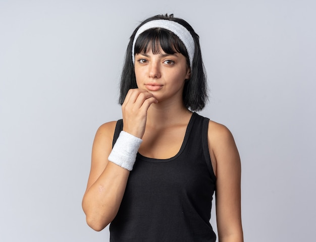 Junge fitness-mädchen mit stirnband blick in die kamera verwirrt stehend auf weißem hintergrund