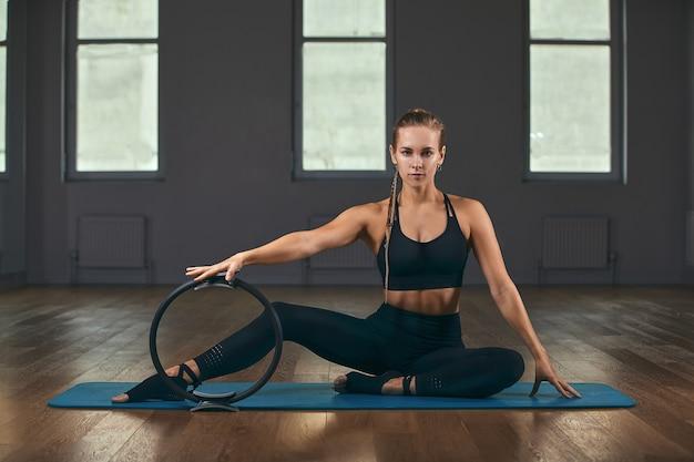 Junge fitness-model-athletin in sportbekleidung, die dehnübungen mit gummiexpander macht. bodybuilding gesunder lebensstil lifestyle konzept bild, kopienraum.