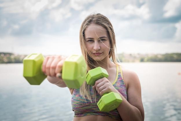 Junge fitness sportliche trener, die übungen mit hanteln am strandsee tun