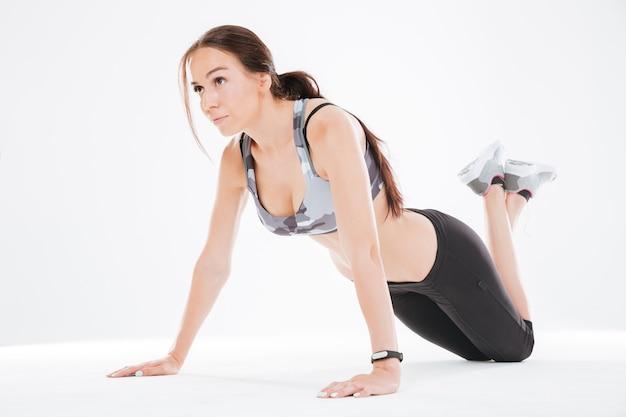 Junge fitnessfrau auf dem boden im studio