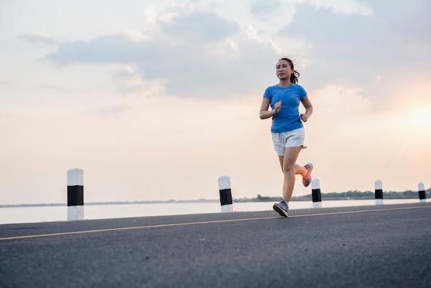 Junge fitnessfrau des gesunden lebensstils, die am flussufer läuft.