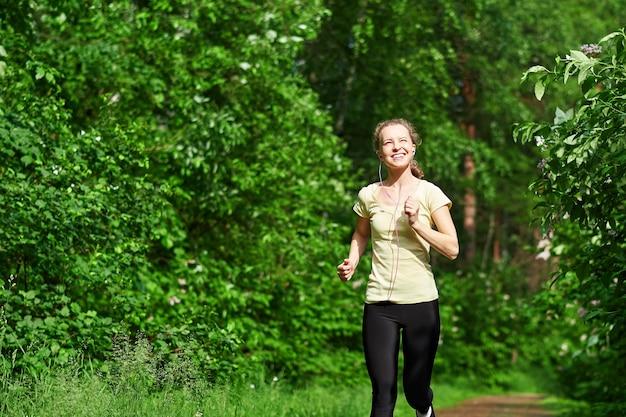 Junge fitnessfrau, die am waldweg läuft.