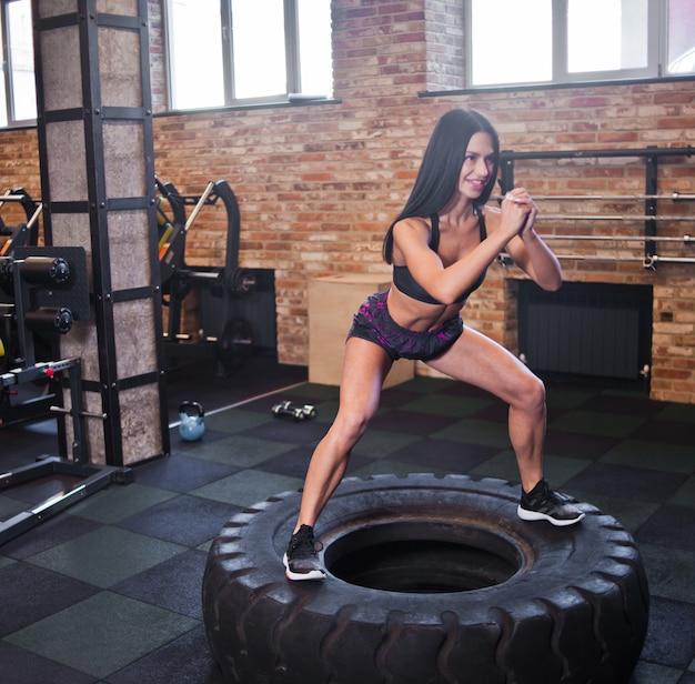 Junge fitnessfrau, die auf einem großen rad in der turnhalle herausspringt