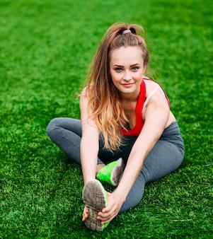 Junge fitnessfrau, die auf grünem gras sitzt.