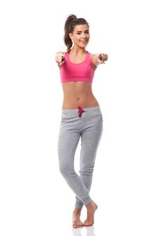 Junge fitnessfrau, die auf kameraseite zeigt