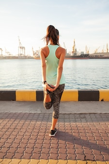 Junge fitnessfrau, die beine ausdehnt, bevor sie in der stadt in der nähe des seehafens gelaufen ist?