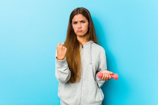 Junge fitnessfrau, die ein gewicht hält, das faust zur kamera, aggressiven gesichtsausdruck zeigt.