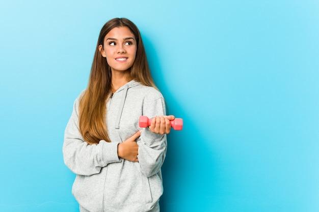 Junge fitnessfrau, die ein gewicht hält, das zuversichtlich mit verschränkten armen lächelt.