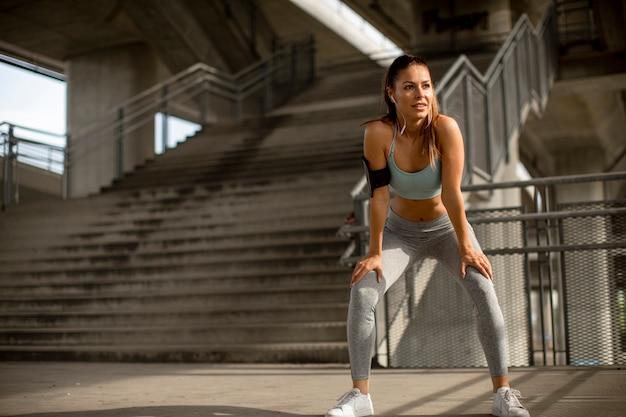 Junge fitnessfrau, die eine pause vom laufen in der städtischen umgebung macht