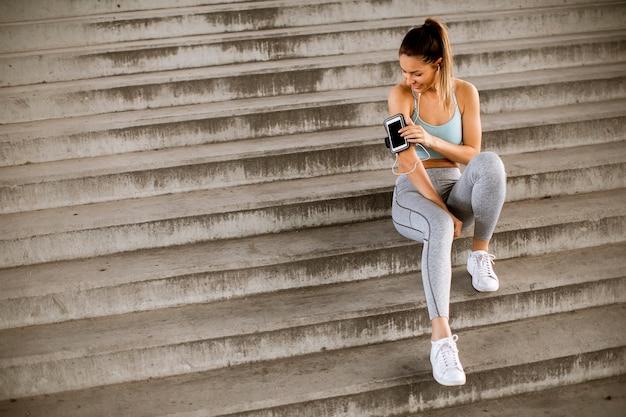 Junge fitnessfrau, die eine pause vom laufen macht, das auf stufen sitzt und handy in armband verklagt