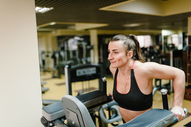 Junge fitnessfrau, die hängt und arbeitet, die mit bauchmuskeln arbeitet, drücken auf den horizontalen balken im gymnastikclub