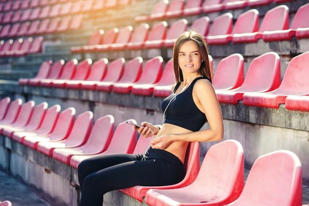 Junge fitnessfrau, die musik auf smartphone hört
