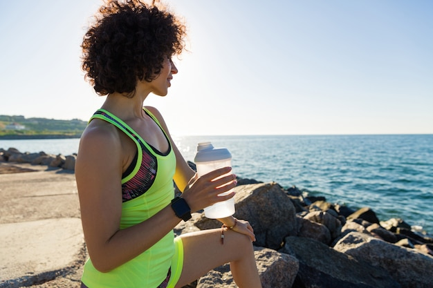 Junge fitnessfrau, die nach dem joggen ruht