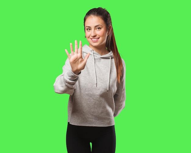 Junge fitnessfrau, die nummer fünf zeigt
