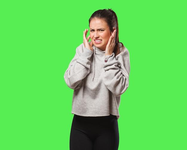 Junge fitnessfrau, die ohren mit händen bedeckt