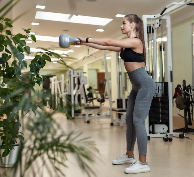 Junge fitnessfrau, die ruckübung mit kettlebell im fitnessstudio tut. funktionstraining mit freien gewichten