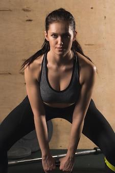 Junge fitnessfrau, die schwere kesselglocke im fitnessstudio hebt