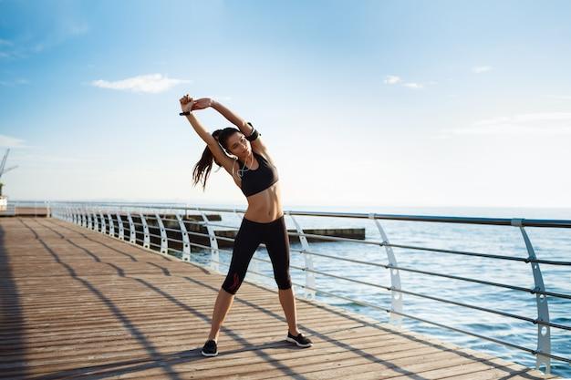 Junge fitnessfrau, die sportübungen mit seeküste hinter macht