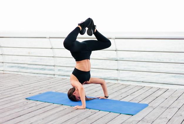 Junge fitnessfrau, die yoga-übungen macht, die auf ihrem kopf auf einer turnmatte am strand stehen