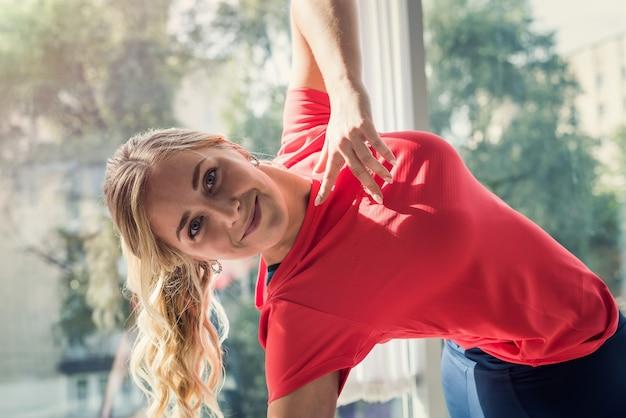Junge fitnessfrau, die yogaübung nahe dem fenster während der quarantäne im süßen haus tut