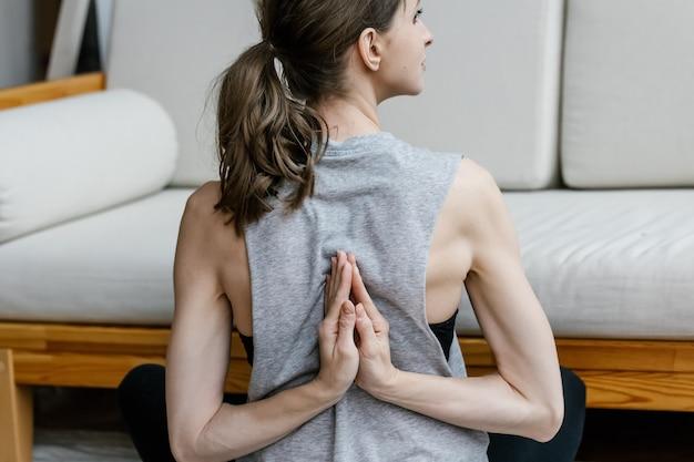 Junge fitnessfrau, die zu hause innenraum streckt