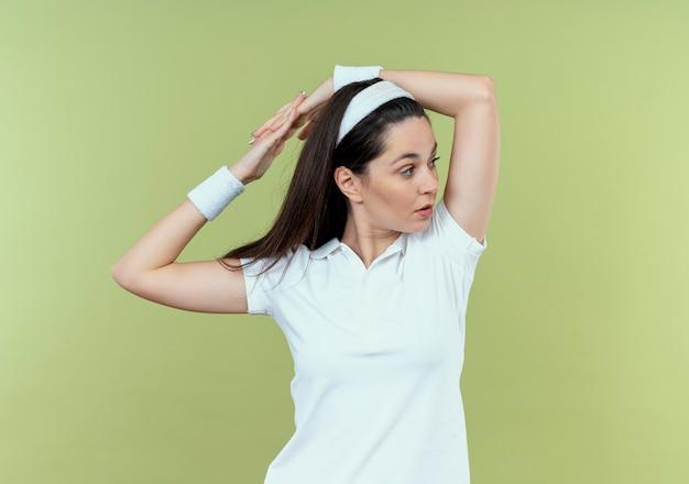 Junge fitnessfrau im stirnband, das beiseite schaut, das ihre hände über hellem hintergrund stehend streckt