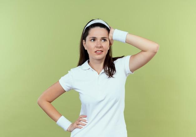 Junge fitnessfrau im stirnband, das beiseite schaut, verwirrt mit hand auf ihrem kopf, der über lichtwand steht