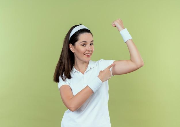 Junge fitnessfrau im stirnband, das die faust hebt, zeigt den bizeps lächelnd, der zuversichtlich über der hellen wand steht