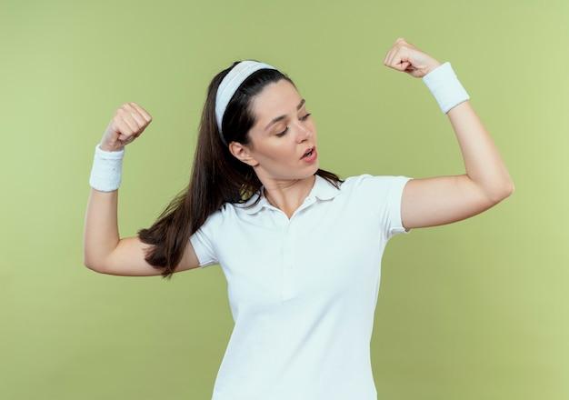 Junge fitnessfrau im stirnband, das fäuste erhebt, die bizeps zeigen, der zuversichtlich steht, über heller wand zu stehen