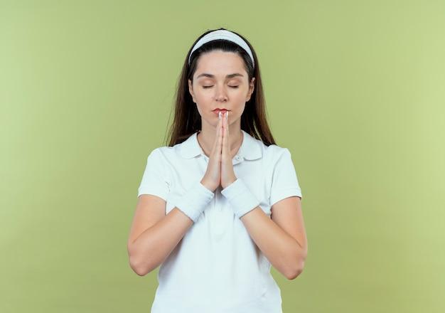 Junge fitnessfrau im stirnband, das hände zusammenhält, wie das beten mit geschlossenen augen steht über hellem hintergrund