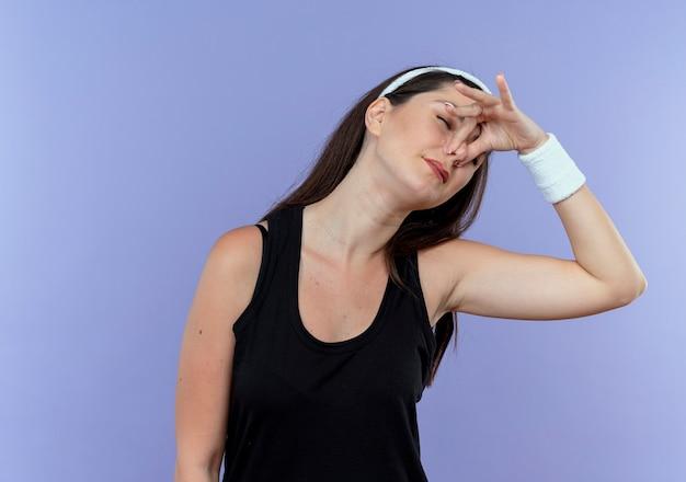 Junge fitnessfrau im stirnband, das ihre nase mit den fingern über blauem hintergrund schließt