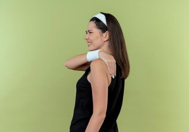 Junge fitnessfrau im stirnband, das ihre schulter berührt, fühlt schmerz, der unzufrieden steht, über heller wand stehend