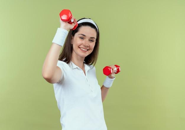 Junge fitnessfrau im stirnband, das mit den hanteln herausarbeitet, die glücklich und positiv über hellem hintergrund lächeln