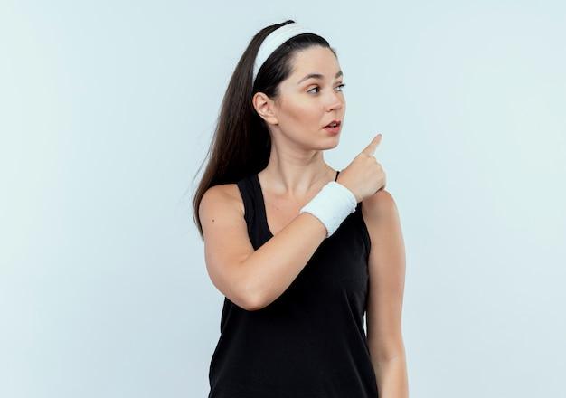 Junge fitnessfrau im stirnband, das mit ernstem gesicht beiseite schaut, das mit ndex finger auf etwas zeigt, das über weißem hintergrund steht