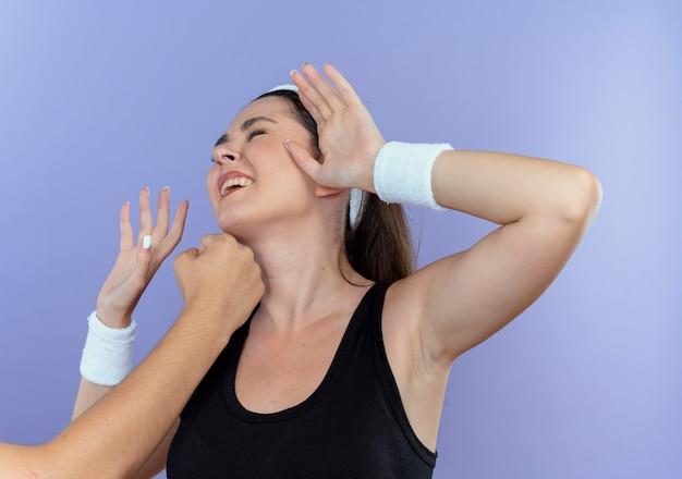 Junge fitnessfrau im stirnband, das mit faust in ihrem gesicht gestanden wird, das über blauem hintergrund steht