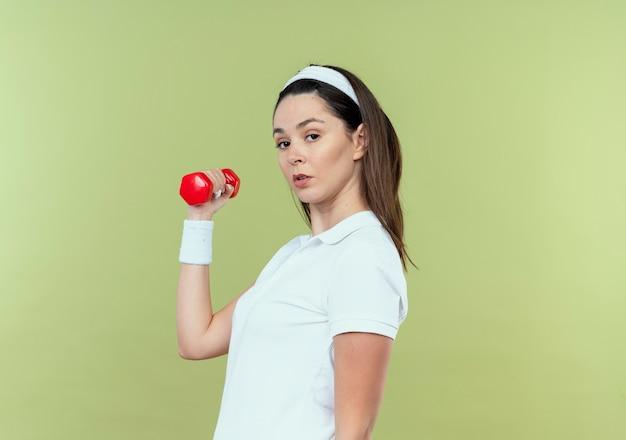 Junge fitnessfrau im stirnband, das mit hantel arbeitet, die kamera mit ernstem gesicht betrachtet, das über hellem hintergrund steht