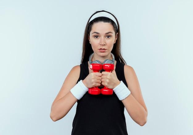 Junge fitnessfrau im stirnband, das mit hanteln arbeitet, die kamera mit ernstem gesicht betrachten, das über weißem hintergrund steht