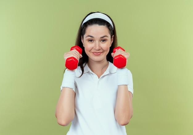 Junge fitnessfrau im stirnband, das mit hanteln arbeitet, die sicher lächelnd über hellem hintergrund stehend schauen