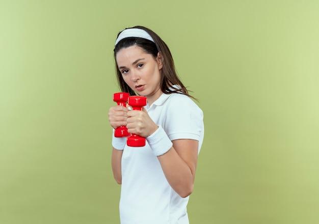 Junge fitnessfrau im stirnband, das mit hanteln arbeitet, die sicher stehen über heller wand stehen